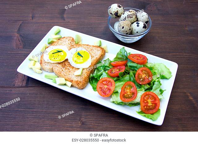 Toast with quail eggs and salad on a wooden table