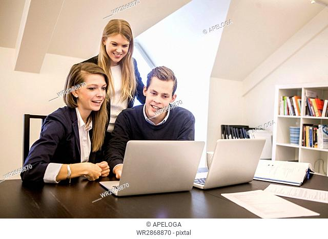 Young businessman with women discussing with laptops during meeting at office