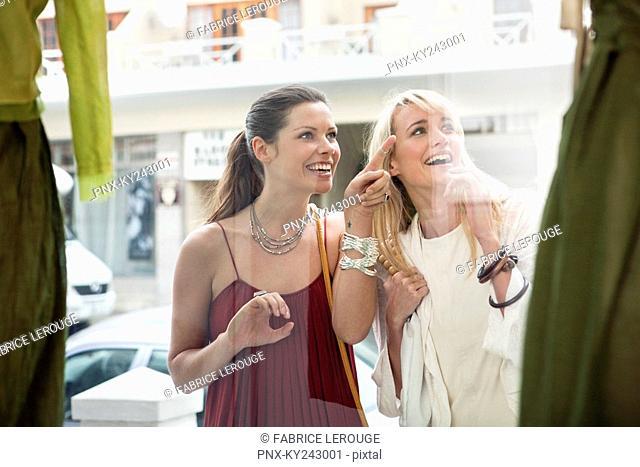 Two women window shopping outside a store