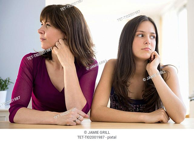 Frustrated teenage girl (14-15) and her mom sitting at table