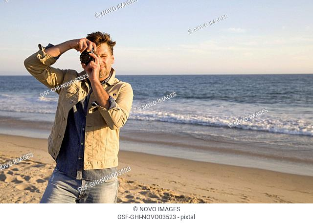 Mid-Adult Man Looking Through Camera Lens at Beach