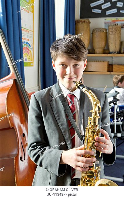 Portrait confident middle school student with saxophone in music classroom