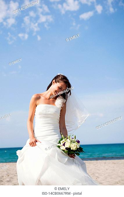 bride holding the bridal bouquet on beach
