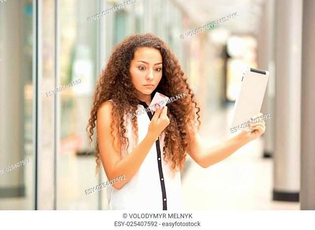 Beautiful young girl paying by credit card for shopping with a laptop against the background of the shopping center