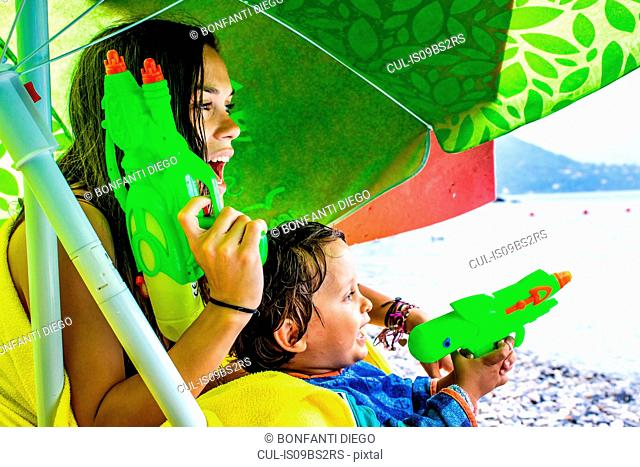 Woman and boy playing with water pistols on beach