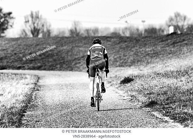 Bath - the Netherlands - A cyclist riding along the Westerschelde on a bike
