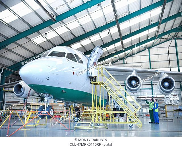 Workers inspecting jet aircraft in hangar