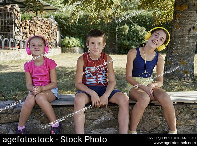 Three kids smile in front of the camera while