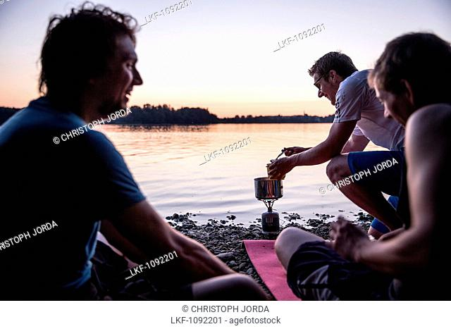 Three young men camping at a lake, Freilassing, Bavaria, Germany