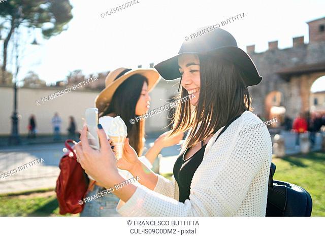 Woman taking selfie with ice cream cone, Pisa, Toscana, Italy