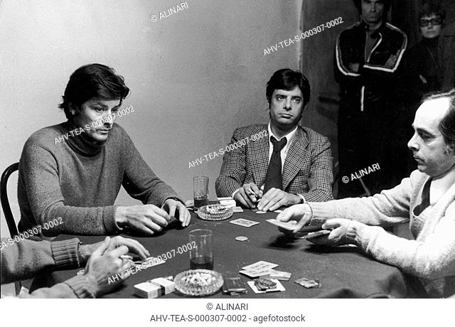 Alain Delon and Giancarlo Giannini playing cards with two other people, shot 1970 - 1980 by Team
