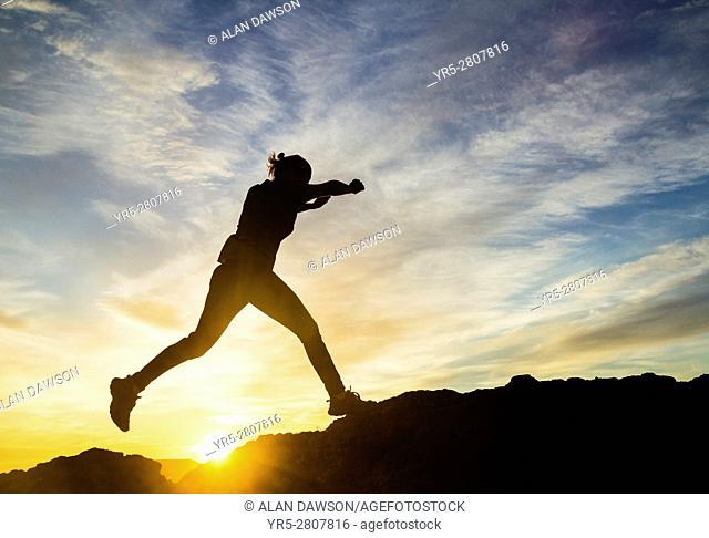 Mature female jogger at sunrise on volcanic mountain overlooking Las Palmas city. La Isleta, Las Palmas, Gran Canaria, Canary Islands, Spain