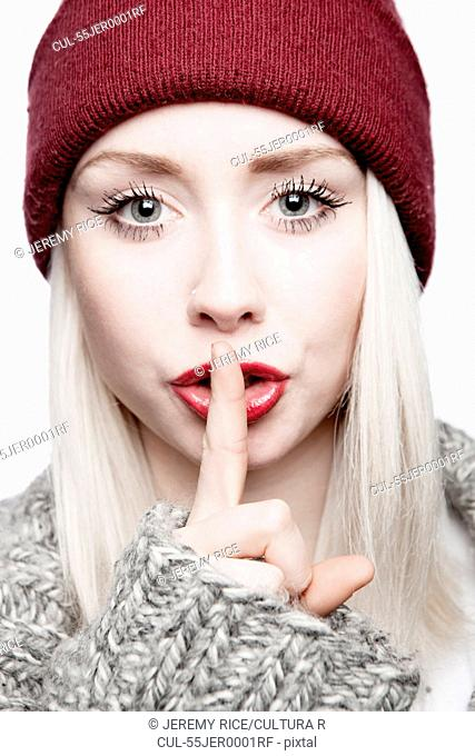 Young woman wearing red hat with finger on lips