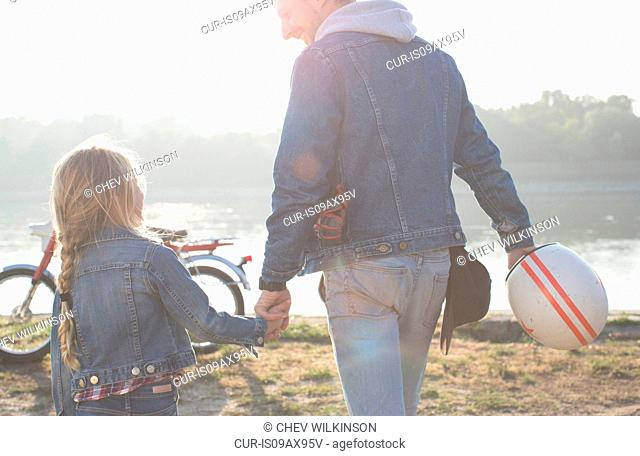 Father and daughter, holding hands, beside lake, rear view