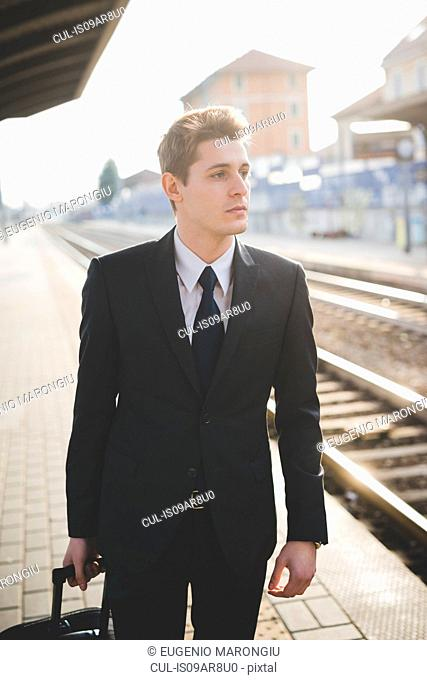 Portrait of young businessman commuter standing on railway platform