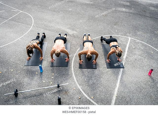 Sporty team during workout, pushups