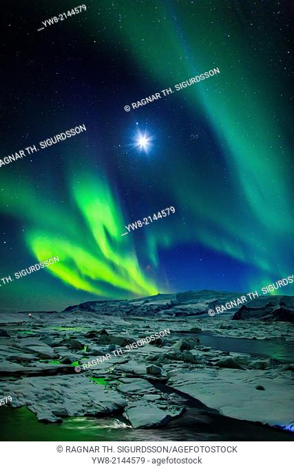Moon and Aurora Borealis. Northern lights with the moon illuminating the skies and icebergs at the Jokulsarlon Glacial lagoon, Iceland