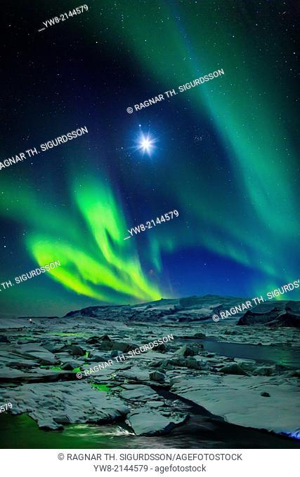 Moon and Aurora Borealis. Northern lights with the moon illuminating the skies and icebergs at the Jokulsarlon Glacial lagoon, Iceland