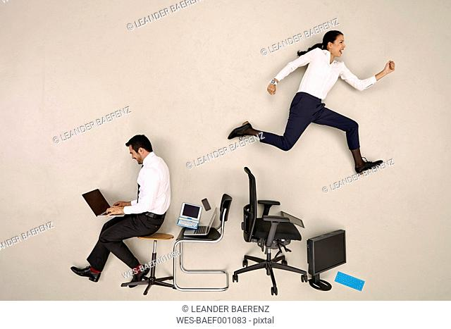 Businessman sitting and working, female colleague jumping over chairs