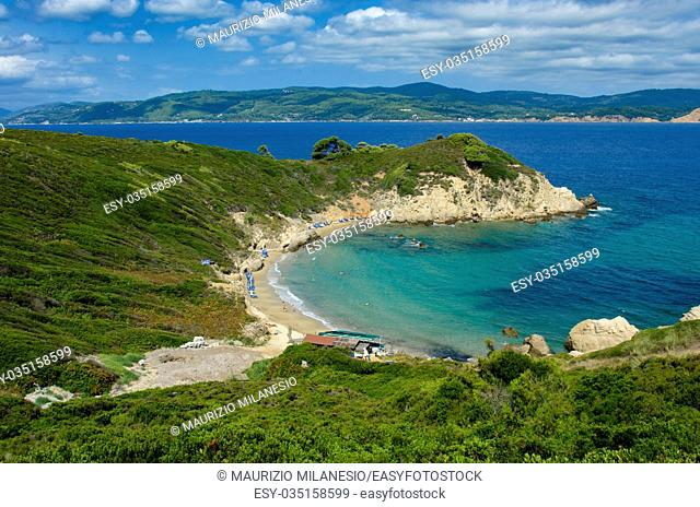 View from the top of the beach of Krifi Amos on the island of Skiathos Greece, the sea is green and turquoise surrounded by rich vegetation