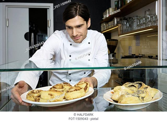 Male chef keeping cinnamon rolls for retail display at cafe