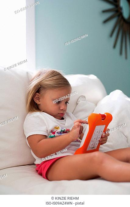 Girl sitting on sofa using handheld video game