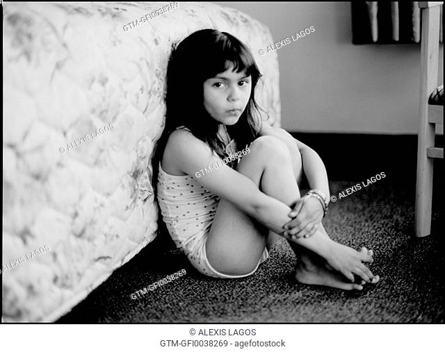 Portrait of a seven year old girl seated on carpet against a hotel bed
