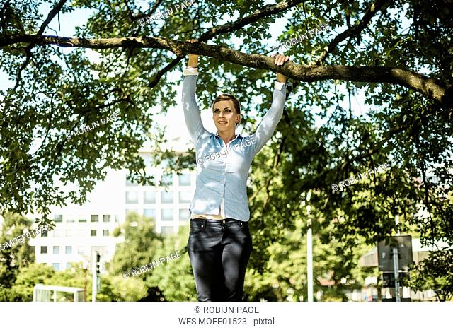 Woman in urban park hanging at branch of a tree