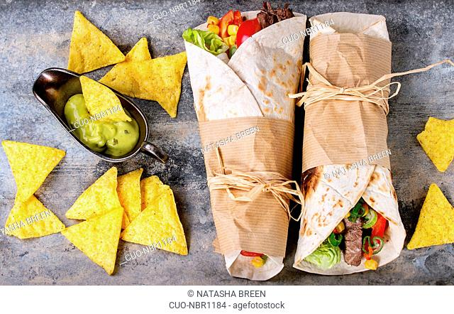 Mexican style dinner. Two papered tortillas burrito with beef and vegetables served with nachos chips and guacomole sauce over old textured tin background
