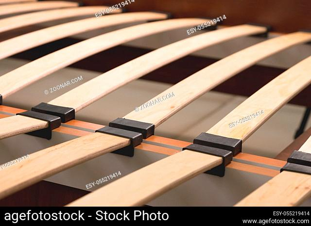 Close-up wooden elements of an arthopedic base of a double bed. Interior structure of furniture