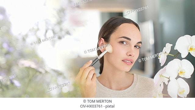 Brunette woman applying makeup with powder brush