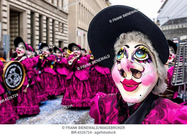 Members of the Gugge marching brass bands wearing fancy dresses and masks at the great procession at the Carnival of Basel, Basler Fasnacht, Basel, Switzerland