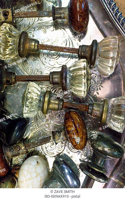 Overhead view with variety of antique doorknobs on silver tray