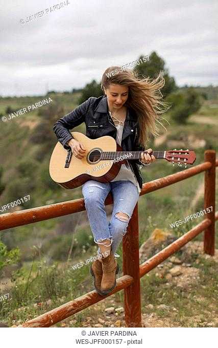 Woman sitting on wooden fence playing guitar