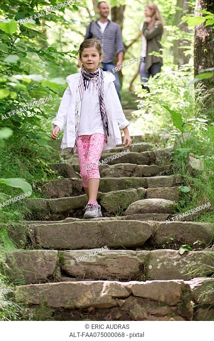 Girl walking down stone steps in woods, parents in background