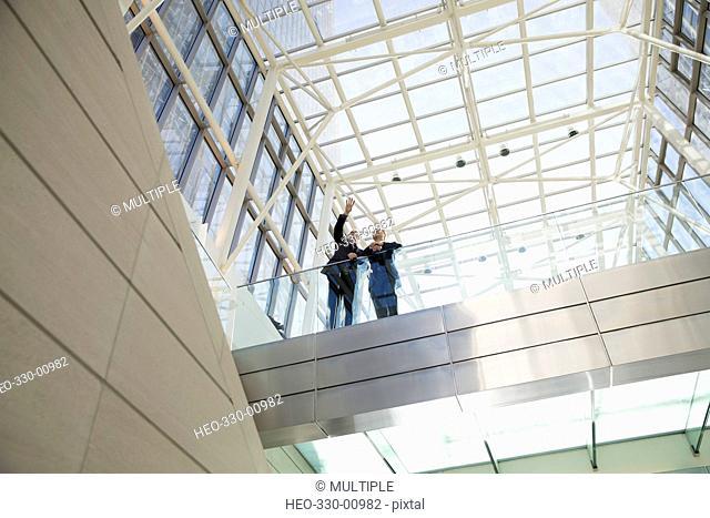 Businessmen talking on atrium balcony