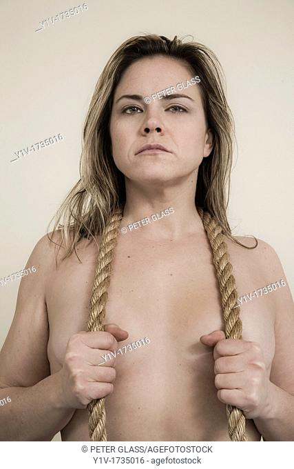 Woman holding a piece of rope around her neck