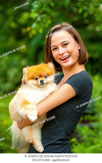 An 18 year old woman holding a Pomeranian dog and looking at the camera