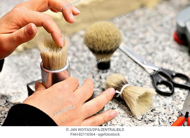 An employee of the company Hans-Juergen Mueller GmbH moulds a bundle of badger hair for a shaving brush in Stuetzengruen, Germany, 24 May 2016