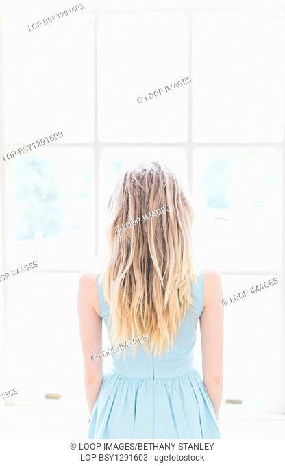 A blonde girl looking out of a window