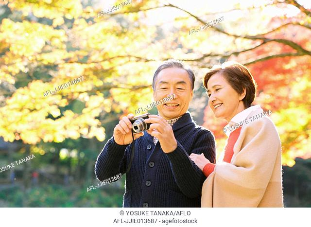 Senior Japanese couple taking pictures in a traditional park in Autumn