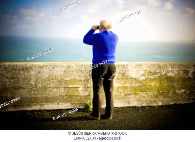 Old man looking through binoculars in Galicia, Spain