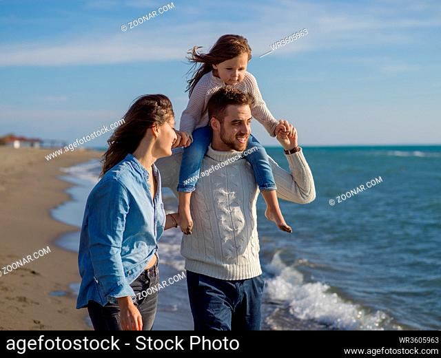 Family with little daughter resting and having fun at beach during autumn day