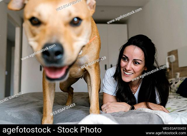 Smiling woman looking at dog while lying on bed at home