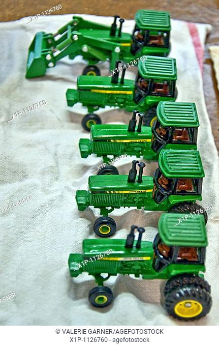 This vertical image shows a row of 5 green John Deere vintage toy tractors being prepped for an antique show, freshly washed and drying on a towel Focus is...