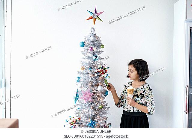 Girl with ice cream next to christmas tree