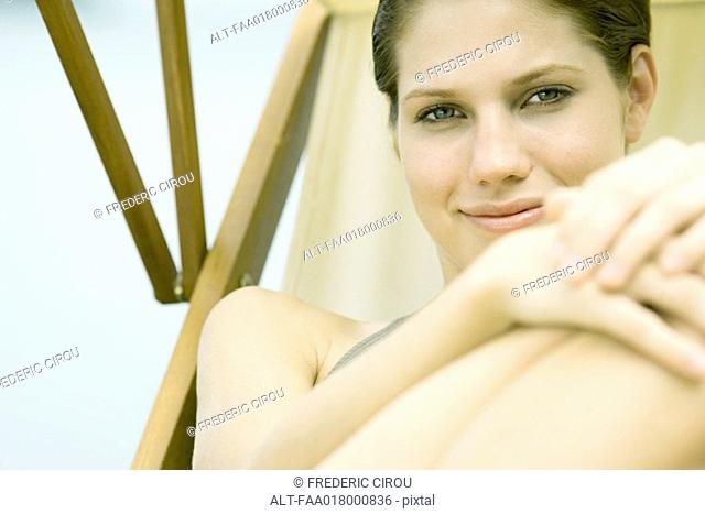 Young woman lounging in beach chair, smiling at camera