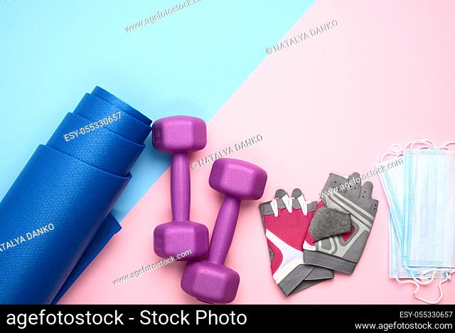 pair gloves, blue neoprene mat, medical face mask and a pair of dumbbells. Sports concept during epidemics, pandemic, top view