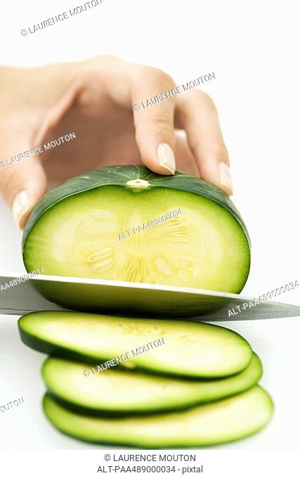 Woman slicing squash zapallito redondo with knife, cropped view of hand