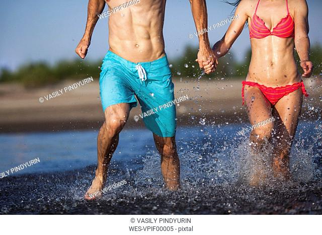 Couple holding hands splashing in water